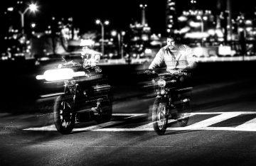 Auf der Straße fahrende Moped- und Motorradfahrer, die beschleunigen