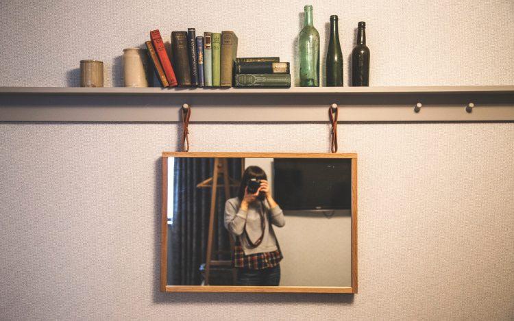 Frau fotografiert sich vor dem Spiegel
