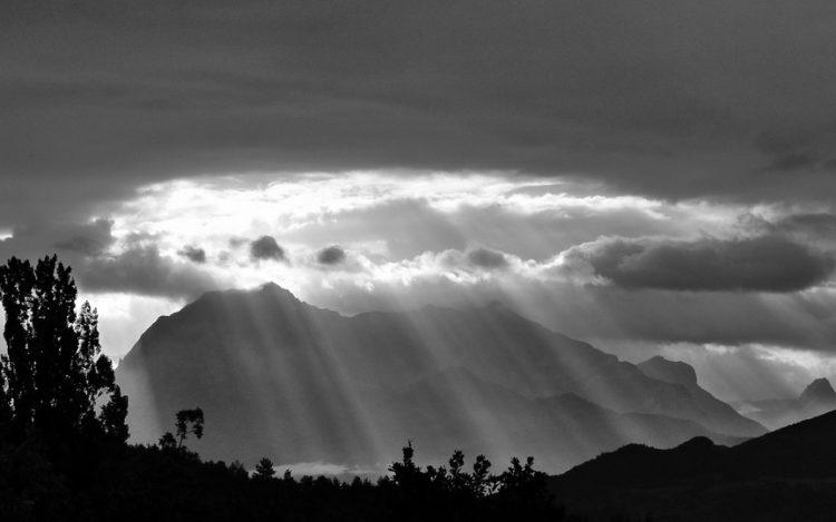 Berge in den Alpen. Die Sonne bricht durch die Wolkendecke