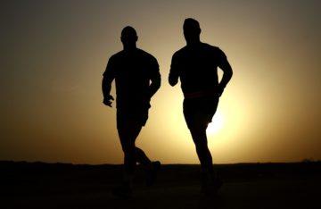 Silhouette von zwei Männern, die nebeneinander joggen