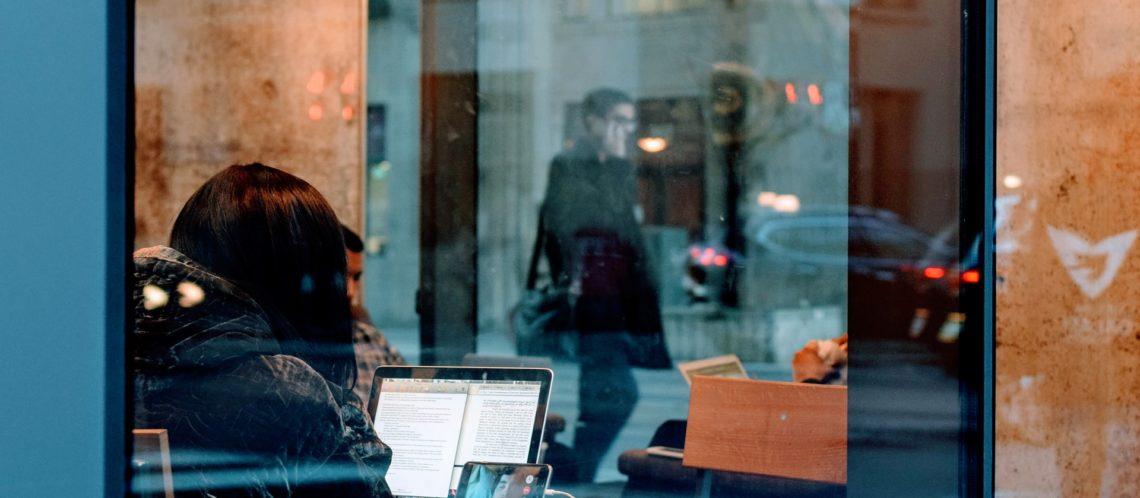 Blick in ein Fenster Frau vor Laptop und Smartphone Spiegelung der Straße und von vorbeilaufenden Menschen symbolisiert zwei Persönlichkeiten: Die digitale Identität und die reale Identität