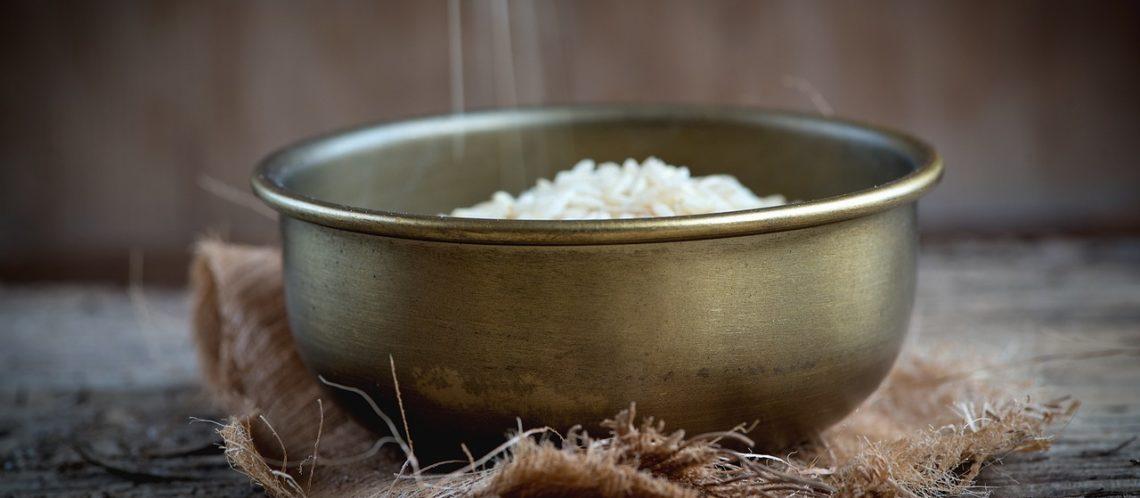 Reis wird in silberne Schüssel geschüttet