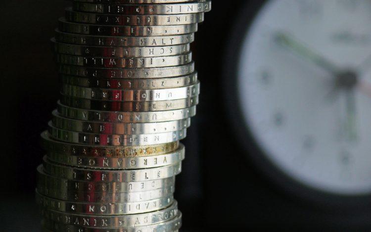 Euromünzen gestapelt vor dem Hintergrund einer verschwommenen Uhr