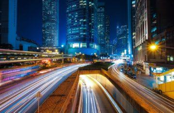 Beschleunigte Straße in Stadt mit Hochhäusern und Lichtern bei NAcht