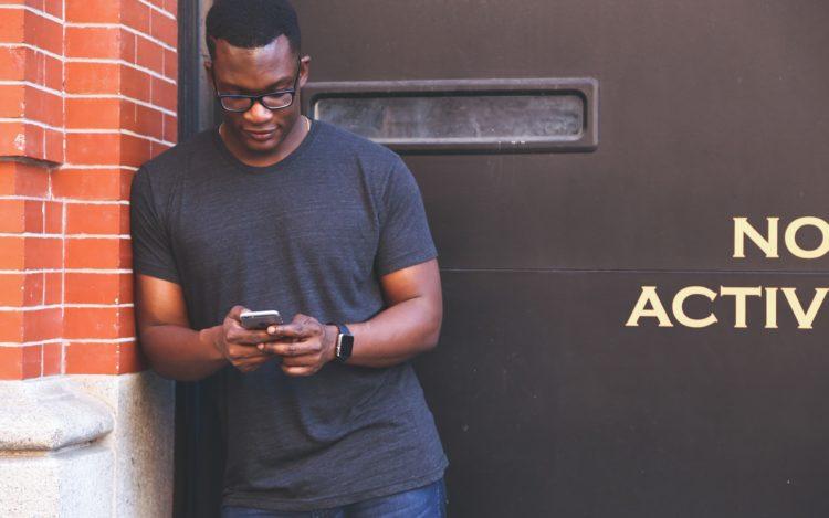 Mann lehnt an Wand und schaut auf sein Smartphone