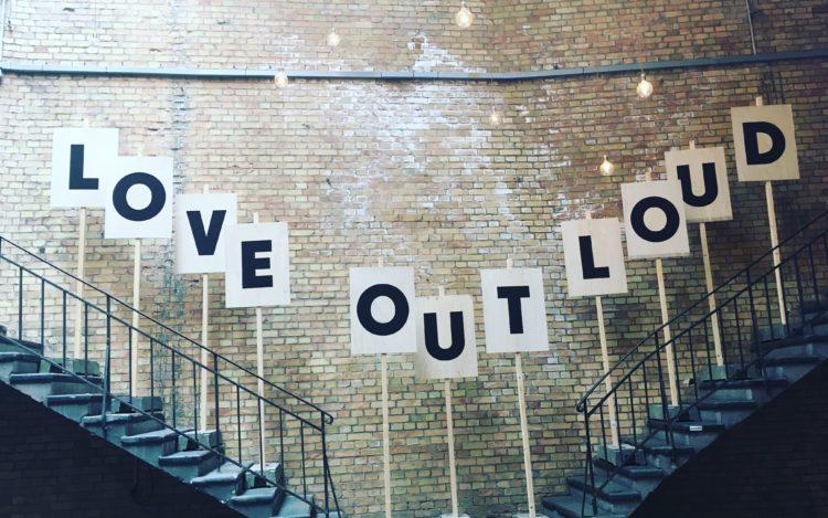 Love out loud Buchstaben auf Papier aufgestellt auf zwei Treppen