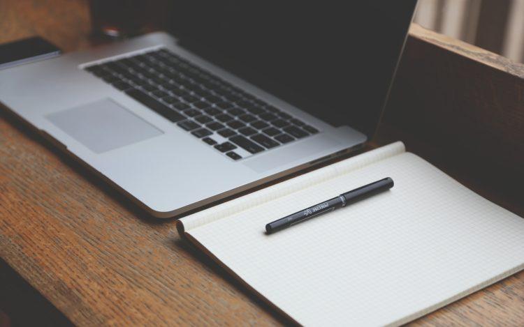 Macbook neben Notizheft und Stift