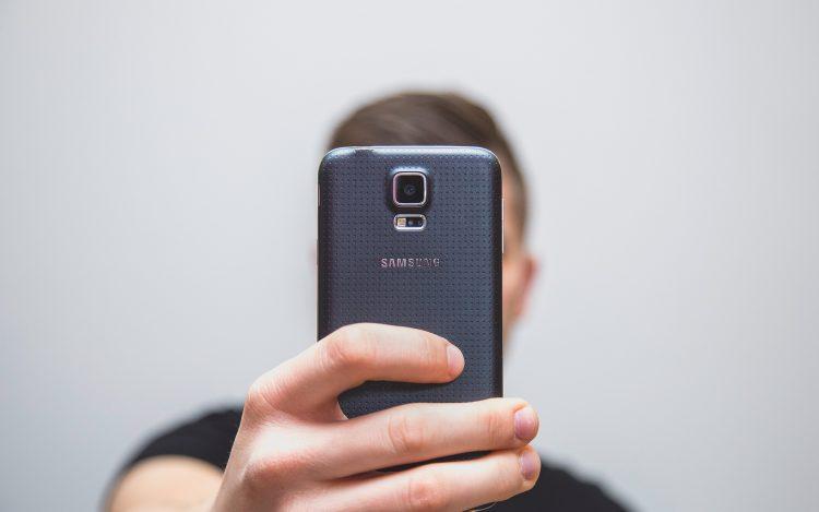 Mann Junge macht mit dem Smartphone ein Selfie Bild oder Video von sich