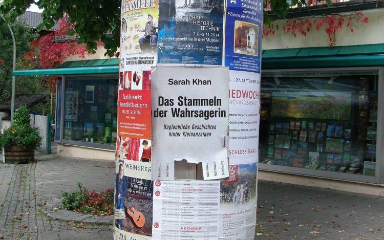 Litfaßsäule mit Plakaten und Anzeigen. In der Mitte das Cover des Buches Das Stammeln der Wahrsagerin über eBay-Geschichten