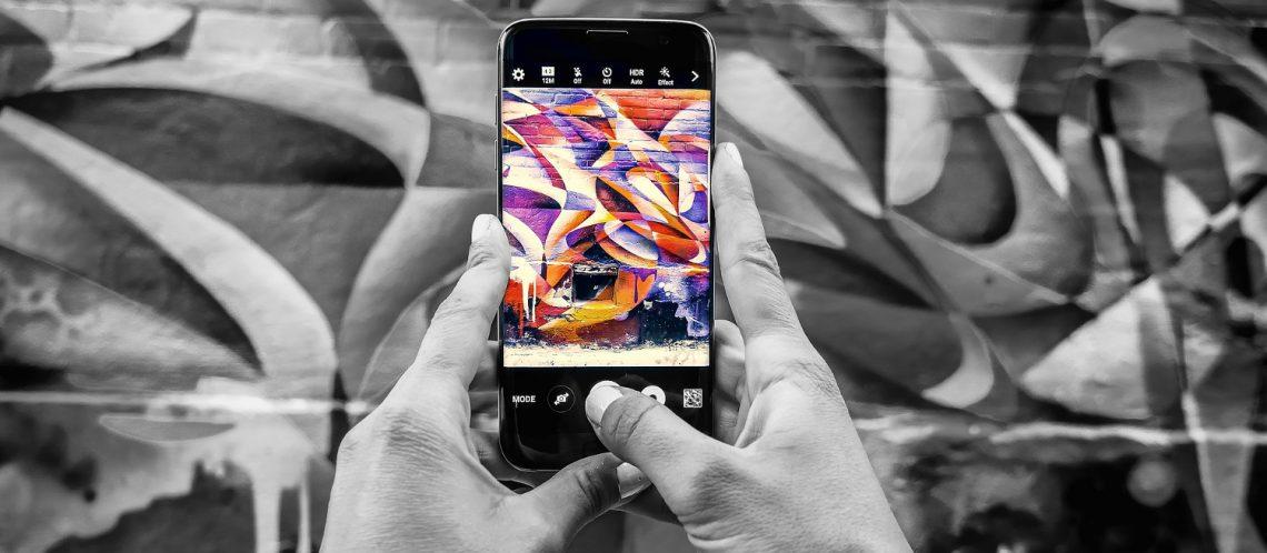 Smartphone wird vor bunte Graffiti Wand gehalten, sodass Streetart online animiert wird