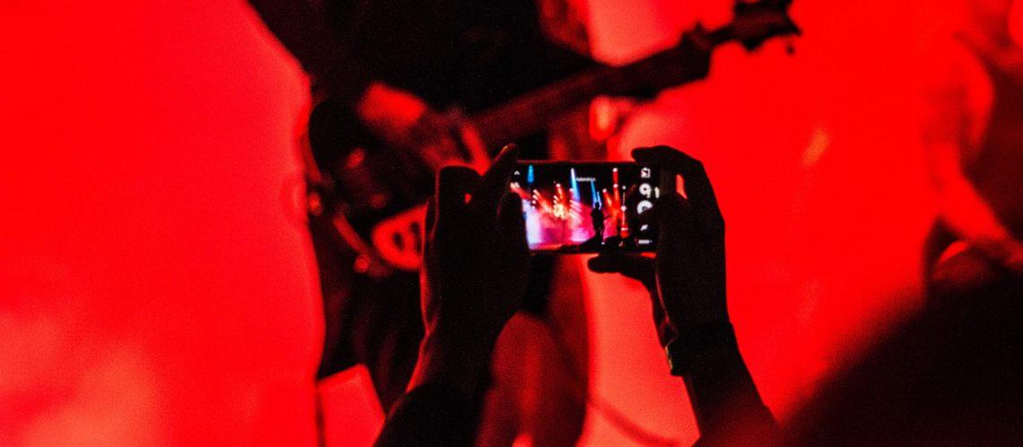 Gitarrist und Musiker auf Bühne mit Smartphone gefilmt zum Artikel: Jeden Tag ein neues Musikvideo dank künstlicher Intelligenz