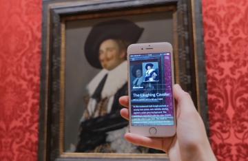 Museen digital: Smartphone wird vor Gemälde gehalten