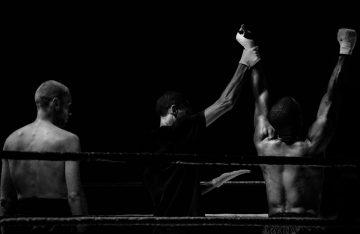 Schwarz-weiß Bild zwei Boxer, Schiedsrichter hält einen Arm hoch, Bild zum Wahlkampf 2017 Artikel