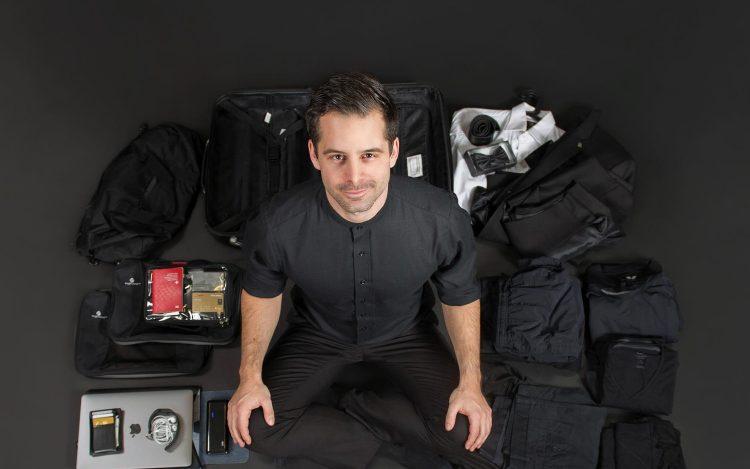 schwarz angezogener Mann viele Gegenstände schwarzer Boden