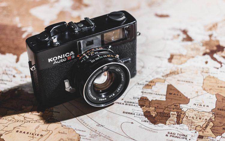 Weltkarte schwarze Kamera zum Artikelthema Reisefotografie: Ein Koffer macht Träume wahr