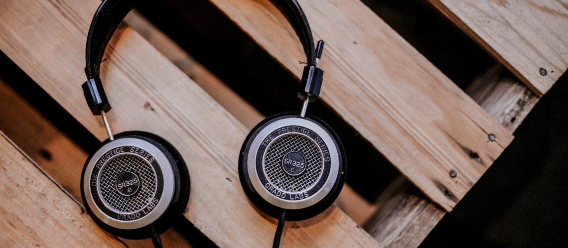 schwarze Kopfhörer, braune Holzkiste