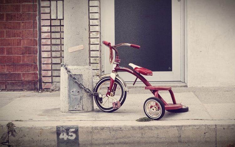 Kinder Dreirad an Laterne angeschlossen auf dem Bürgersteig zum Thema Berliner Kindheitsgeschichten