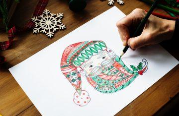 Holztisch Blatt Papier Bild vom Weihnachtsmann bunte Farben Schneeflocken Hand mit Stift zum Artikelthema Viraler Hit auf Twitter: Zweitklässler pfeift auf den Nikolaus