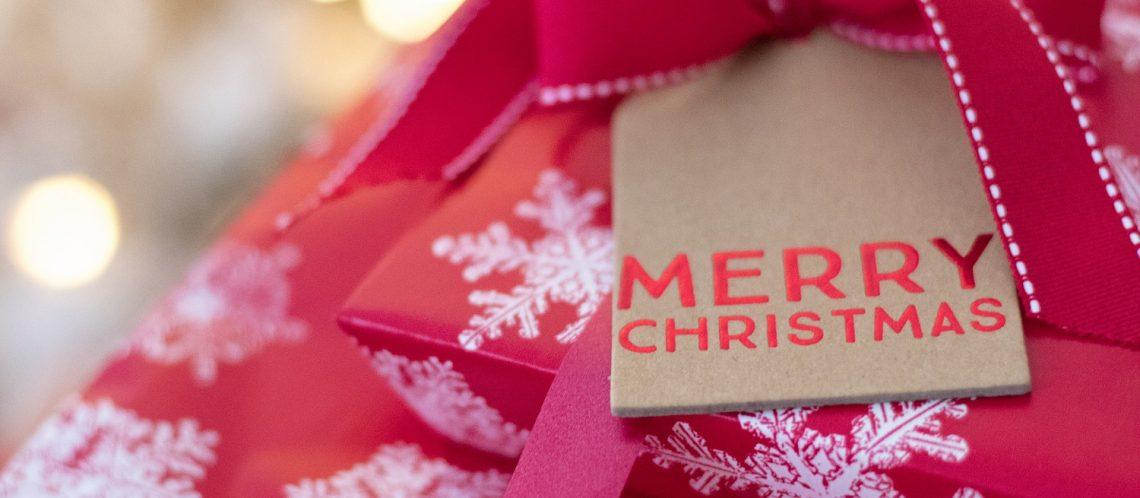 rotes Geschenk Schneeflocken Papierschild Merry Christmas zum Artikelthema Digital XMAS: Wie feiert Deutschland Weihnachten?