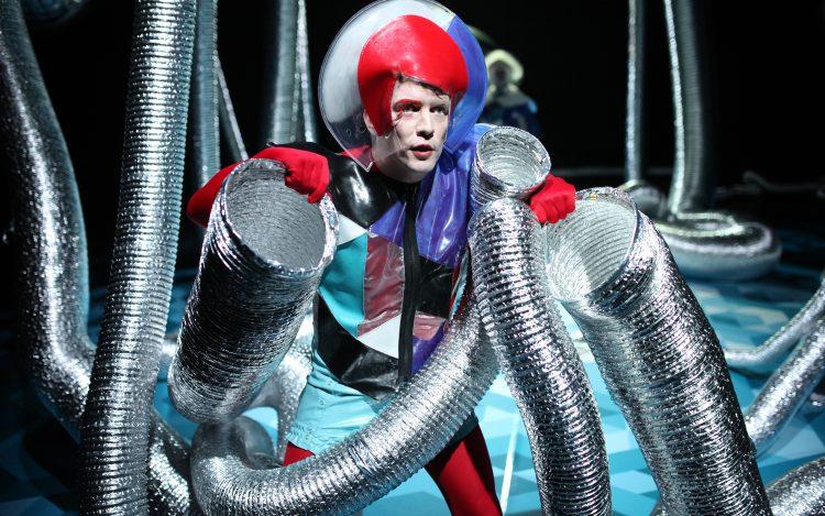 Mann in Kostüm silberne Röhren zu dem Artikelthema Die Maschine steht still nach E. M. Forster: Ist die Technik unser Untergang?