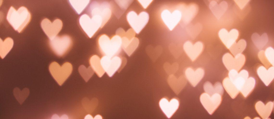 rosa Herzen dunkelroter Hintergrund zum Artikelthema Valentinstag: Top 5 außergewöhnliche Geschenkideen