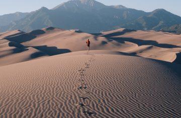 Mensch läuft in Wüste zum Artikelthema Decrustate in der Produzentengalerie Berlin