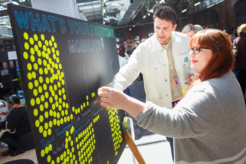 Besucher*innen beschäftigen sich auf der re:publica mit einer Statistik über die Fortbewegungsmittel der Teilnehmer