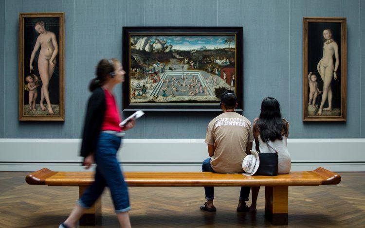 Pärchen im Museum auf der Bank vor Gemälden