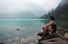 Nachhaltiges Reisen: Frau sitzt am See
